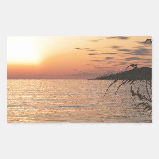 Puesta del sol en el agua pegatina rectangular