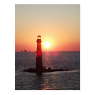 Puesta del sol en el faro de la isla de la arena tarjetas postales