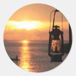 Puesta del sol en la lámpara y la nave de la playa etiqueta