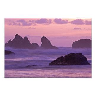 Puesta del sol en las pilas del mar de la playa de foto
