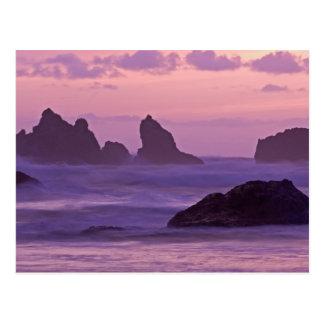 Puesta del sol en las pilas del mar de la playa de tarjetas postales