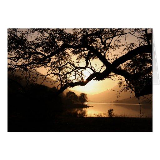 Puesta del sol escocesa a través de un lago tarjeta de felicitación