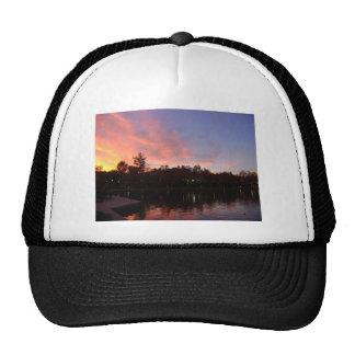 Puesta del sol hermosa sobre el lago gorras
