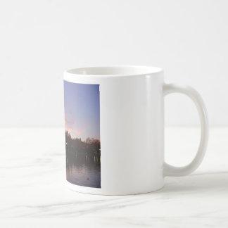 Puesta del sol hermosa sobre el lago tazas de café