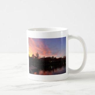 Puesta del sol hermosa sobre el lago taza de café