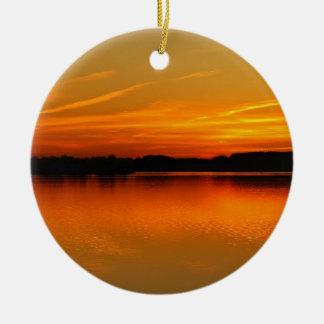 Puesta del sol hermosa sobre paisaje del agua del  adornos de navidad