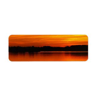 Puesta del sol hermosa sobre paisaje del agua del etiquetas de remite
