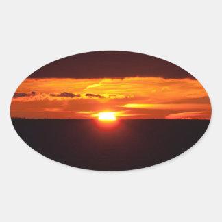 Puesta del sol intensa pegatina ovalada