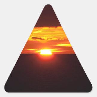 Puesta del sol intensa pegatina triangular