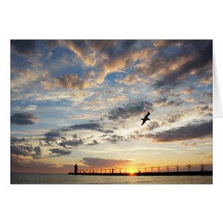 Puesta del sol nublada hermosa sobre el lago felicitación