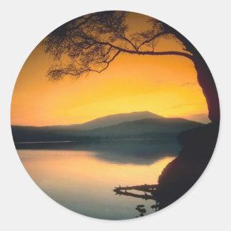Puesta del sol pacífica del lago etiqueta redonda