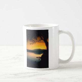 Puesta del sol pacífica del lago taza de café