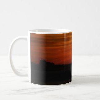 Puesta del sol pintada aceite sobre la taza del