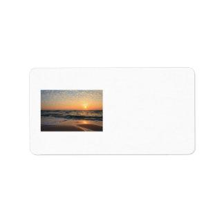 Puesta del sol, playa, y nubes etiqueta de dirección