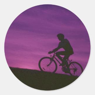Puesta del sol púrpura de ciclo que monta en bicic etiqueta redonda