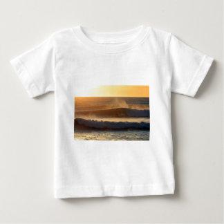 Puesta del sol que practica surf la costa de Nueva Playera De Bebé
