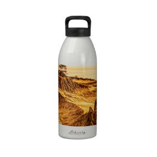 Puesta del sol quebrada de la colina en los pinos  botella de agua
