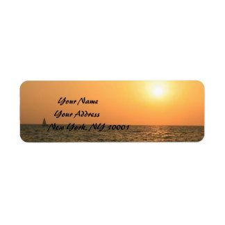 Puesta del sol roja y anaranjada sobre el mar etiqueta de remite