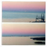 Puesta del sol rosada sobre el agua y la foto queb