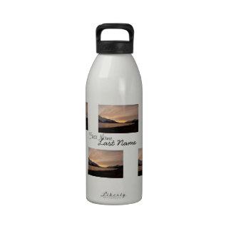 Puesta del sol sobre bahía de la fábrica de conser botella de beber