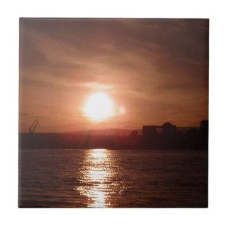 Puesta del sol sobre el lago azulejo cuadrado pequeño