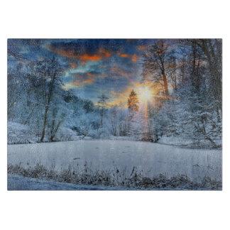 Puesta del sol sobre el lago forest del invierno tablas de cortar