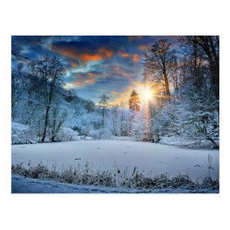Puesta del sol sobre el lago forest del invierno tarjeta postal