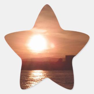 Puesta del sol sobre el lago pegatina en forma de estrella