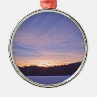 Puesta del sol sobre el lago y árboles nevados adorno navideño redondo de metal