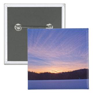Puesta del sol sobre el lago y árboles nevados pin