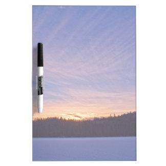 Puesta del sol sobre el lago y árboles nevados pizarras blancas de calidad