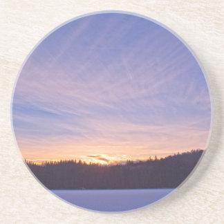 Puesta del sol sobre el lago y árboles nevados posavasos personalizados