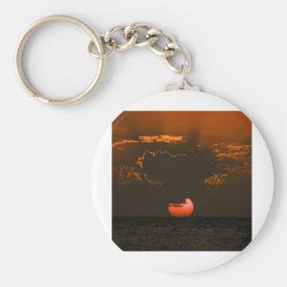 Puesta del sol sobre el océano con las nubes dramá llavero redondo tipo pin