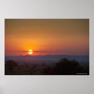 Puesta del sol sobre el paisaje africano póster
