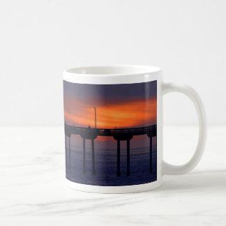 Puesta del sol sobre el puente taza básica blanca
