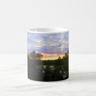 Puesta del sol sobre la charca taza de café