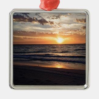 Puesta del sol sobre la playa prístina en la bahía adorno cuadrado plateado