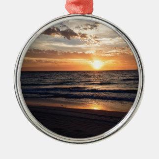 Puesta del sol sobre la playa prístina en la bahía adorno redondo plateado
