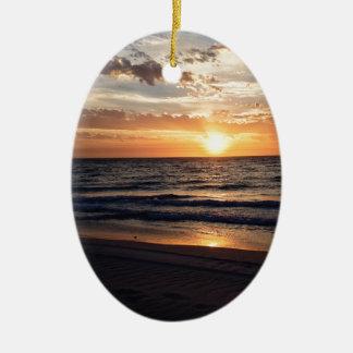 Puesta del sol sobre la playa prístina en la bahía adorno ovalado de cerámica