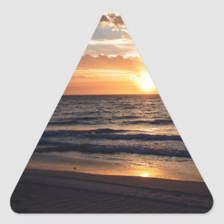 Puesta del sol sobre la playa prístina en la bahía pegatina triangular
