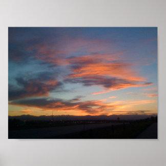 Puesta del sol sobre las siluetas de montañas póster