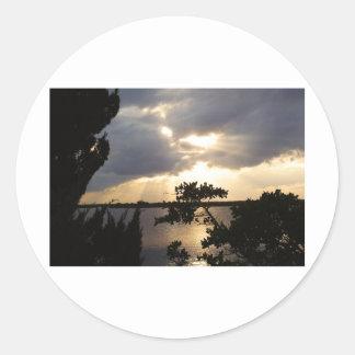 Puesta del sol sobre reserva etiquetas redondas