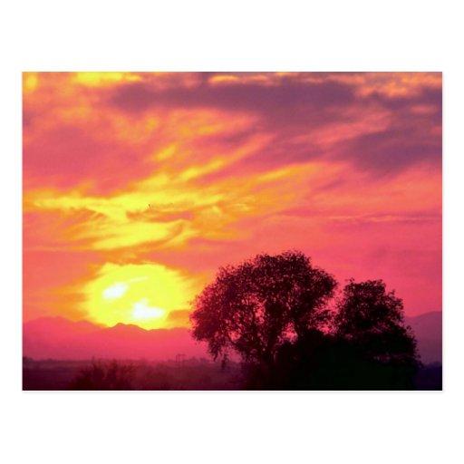 Puesta del sol sobre tierras de labrantío, gran su postal