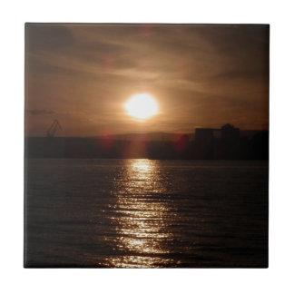 Puesta del sol sobre un lago azulejo cuadrado pequeño