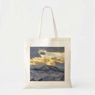Puesta del sol tempestuosa sobre las montañas caps bolsa tela barata