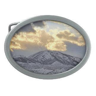Puesta del sol tempestuosa sobre las montañas caps hebillas de cinturon ovales