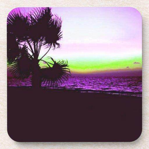 Puesta del sol tropical de la playa y de árboles e posavasos de bebidas