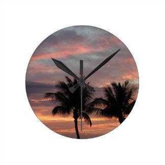 Puesta del sol y palmeras reloj redondo mediano