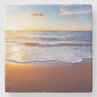 Puesta del sol y playa posavasos de piedra