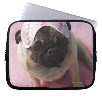 Pug dog with eye mask on head sitting on bed, laptop sleeve